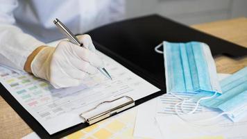médica preenchendo formulário médico na área de transferência segurando a esferográfica. foto