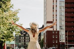 vista traseira de uma jovem mulher feliz em um chapéu de palha em uma cidade europeia. foto