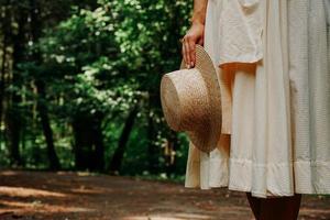 foto de close-up da mão de uma mulher segurando um chapéu de palha