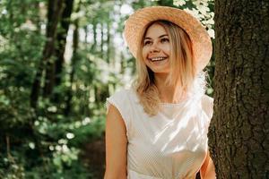linda garota com um chapéu de palha e roupas elegantes fica perto de uma árvore foto