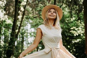jovem com chapéu de palha segurando a bainha de seu vestido branco foto