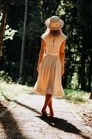 uma jovem com um vestido branco e um chapéu de palha caminha pela floresta foto