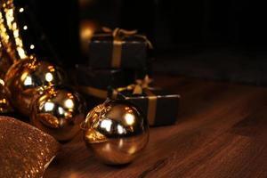 caixa de presente preta com fita dourada e grandes bolas douradas de ano novo em preto foto
