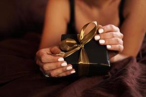 a mulher abre um presente em uma caixa preta com uma fita dourada foto