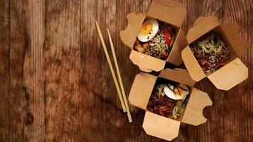 macarrão chinês com frango em caixas de papelão em um fundo de madeira foto