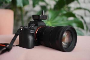 câmera preta com uma lente em um fundo desfocado de folhas verdes. foto