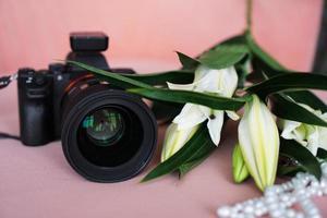câmera preta com lente e lírios brancos e um colar de pérolas foto