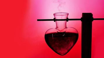 Abra uma garrafa em forma de coração de poção do amor vermelha em um fundo desfocado foto
