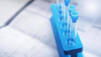 tubos de ensaio em um suporte azul contra uma folha borrada com resultados de teste foto