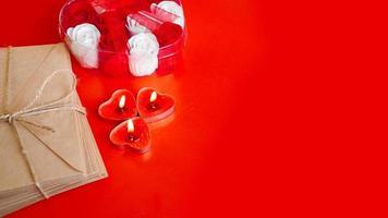 envelopes de papel kraft com velas vermelhas em um fundo vermelho. foto