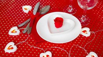 um prato branco com uma faca e um garfo em um fundo vermelho brilhante foto