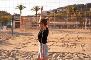retrato de uma mulher atraente perto da rede de vôlei na praia foto