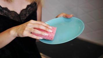 prato azul com esponja de prato rosa na mão no fundo desfocado foto
