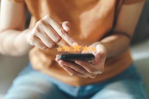 cliente mulher dar cinco estrelas no smartphone. classificação, satisfação. foto