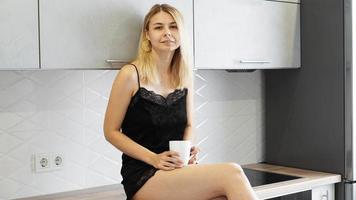 mulher alegre se senta na bancada na cozinha moderna branca. foto