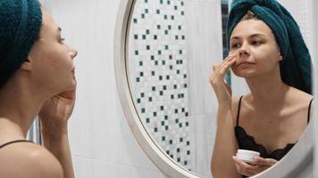 uma foto de uma jovem mulher bonita aplicando loção no rosto
