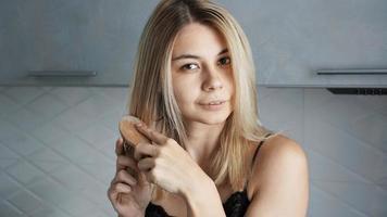 jovem linda mulher alisando o cabelo foto