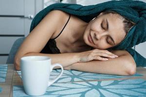 mulher cansada dormindo na mesa. manhã preguiçosa e sonolenta foto