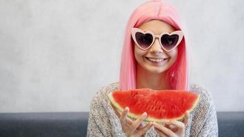 mulher com pedaço de melancia. mulher usa peruca rosa e óculos foto