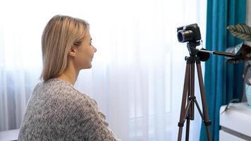 jovem com roupas casuais grava a si mesma na câmera no tripé foto