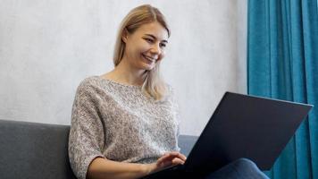 jovem casual usando laptop na sala de estar foto