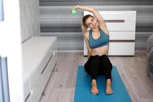 mulher atlética fazendo exercícios com halteres em casa foto