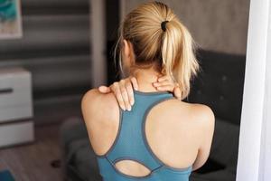 conceito de lesão esportiva. menina atlética sentindo dor no pescoço foto