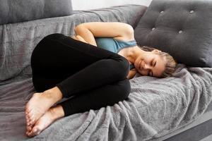 após o treino. bela jovem dormindo no sofá foto