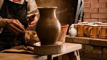 mãos de oleiro fazendo em argila na roda de oleiro foto