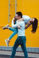 homem feliz carregando sua namorada em fundo amarelo foto