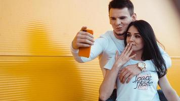 jovem casal adorável fazendo selfie no smartphone sobre fundo amarelo foto