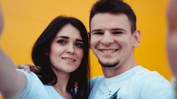 jovem casal adorável fazendo selfie sobre fundo amarelo foto