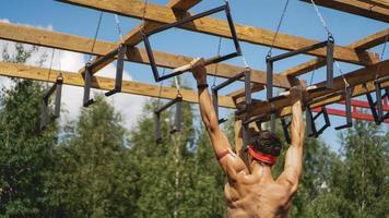 homem passando por obstáculos durante a pista de obstáculos no campo de treinamento foto