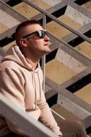 um jovem sentado na escadaria da cidade foto