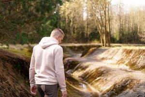 um homem caminha pela floresta próximo a um canal de remo ou rio de montanha foto