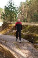 jovem atleta masculino correndo na floresta. homem correndo foto