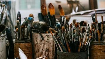 mesa com pincéis e ferramentas na oficina de arte. fundo. foto