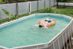 jovem tomando banho de sol em uma banheira inflável na piscina foto