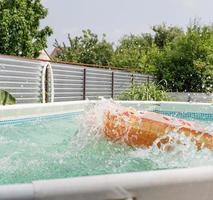 tubo de natação em forma de donut na piscina com respingos foto