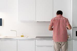 chá de jovem makind ao lado da geladeira aberta. foto