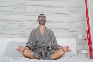 mulher com máscara facial relaxando sentada na cama foto