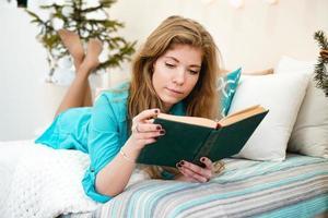jovem lendo um livro enquanto está deitado na cama em casa foto
