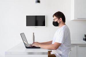jovem com máscara protetora preta trabalhando com laptop de casa foto
