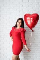 jovem morena de vestido vermelho segurando um balão de coração vermelho foto