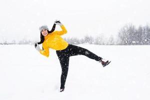 jovem morena brincando com a neve no parque foto