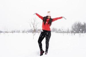 jovem morena de suéter vermelho brincando com a neve no parque foto