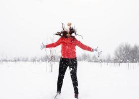 jovem morena despreocupada com um suéter vermelho pulando na neve ao ar livre foto