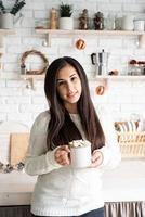 mulher morena segurando uma xícara de chocolate com marshmallow na cozinha foto
