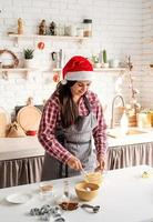 jovem latina mexendo ovos para cozinhar na cozinha foto