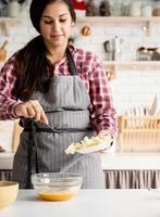 jovem latina cozinhando na cozinha foto